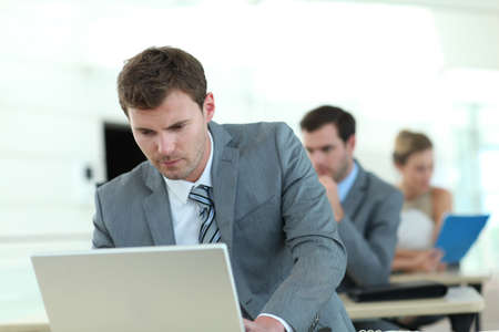 sales executive: Salesman in grey suit attending business training Stock Photo