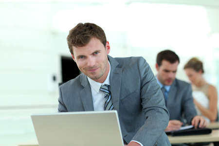 internet class: Salesman in grey suit attending business training Stock Photo