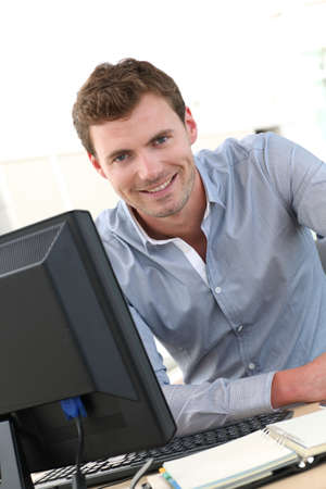officeworker: Handsome office-worker sitting at his desk Stock Photo
