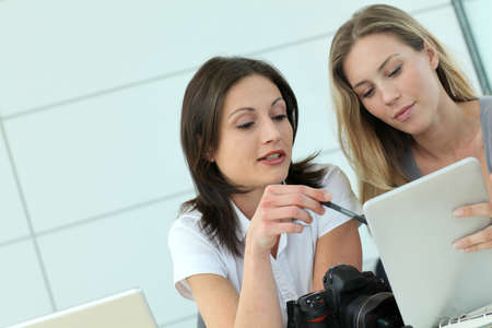 publishing: Women photographers working in office with tablet