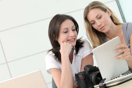 Women photographers working in office with tablet photo