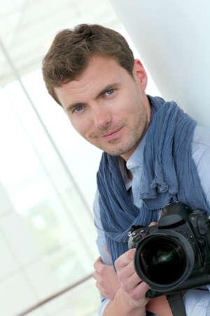 Handsome guy holding photo camera photo