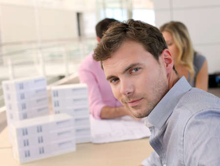 Portrait of man sitting in office with colleagues photo