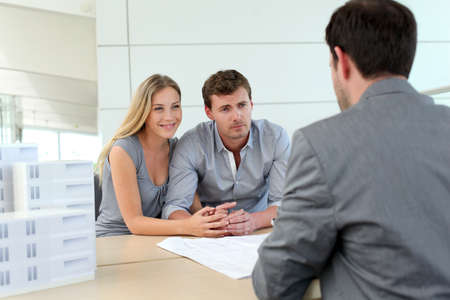 Couple in real-estate agency talking to construction planner photo