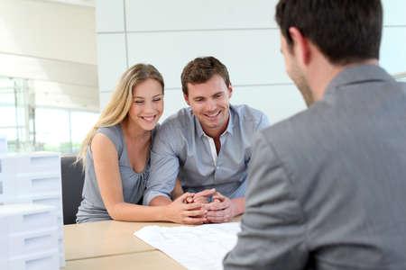 planificaci�n familiar: Pareja en la agencia de bienes ra�ces hablando con planificador de la construcci�n Foto de archivo