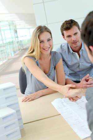 реальный: Пара пожимая руку к агенту по недвижимости в офисе Фото со стока
