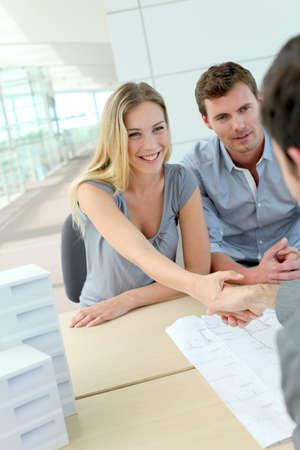 satisfied people: Couple shaking hand to real-estate agent in office Stock Photo
