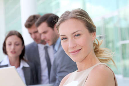Beautiful businesswoman standing outside in front of team photo