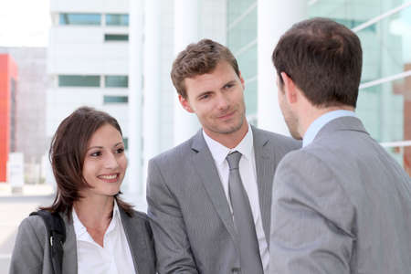 associates: Business people meeting outside office building