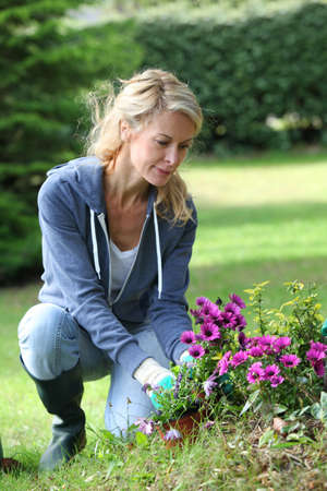 Cheerful blond woman planting flowers in garden photo