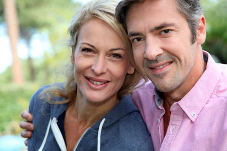 middle aged: Portrait of middle aged couple sitting outside the house