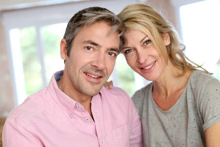 Middle aged couple relaxing in sofa at home photo