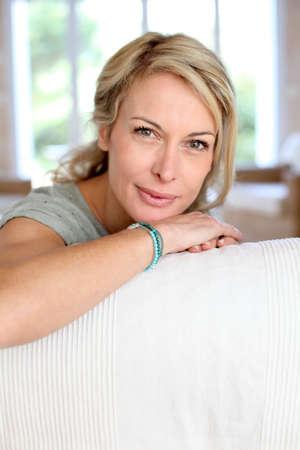 woman 40 years: Beautiful blond mature woman relaxing in sofa