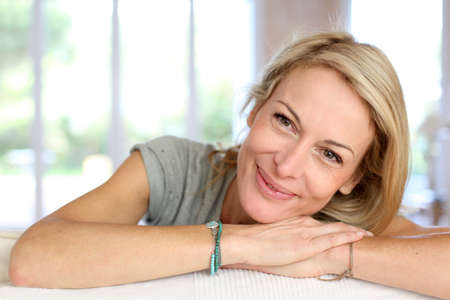 mooie vrouwen: Mooie blonde rijpe vrouw ontspannen in sofa