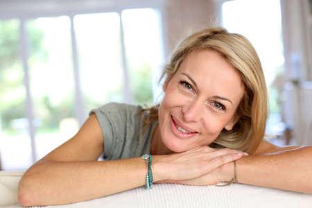 mujeres maduras: Hermosa mujer rubia madura se relaja en un sof�