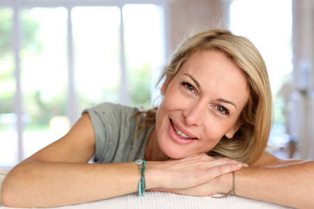 Beautiful blond mature woman relaxing in sofa photo