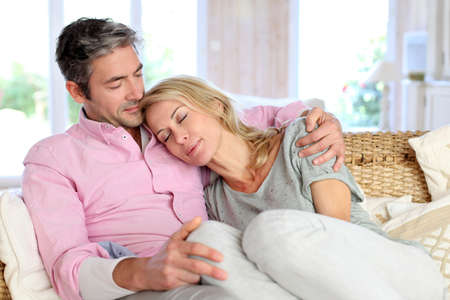 Woman relaxing on husband laid in sofa photo
