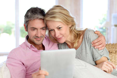 Couple at home using electronic tablet photo