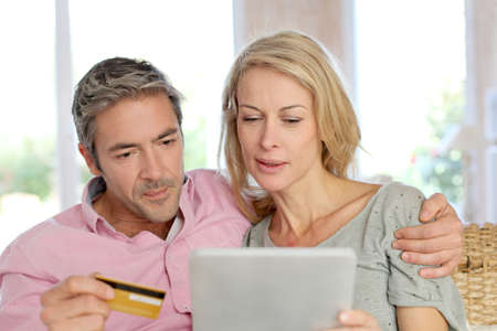 Couple sitting in sofa at home and doing online shopping photo