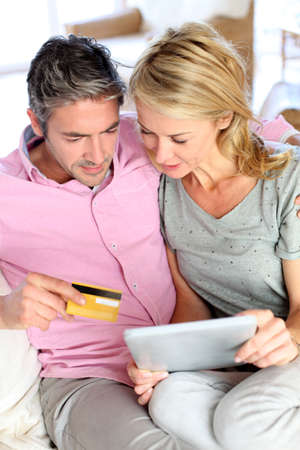 secured payment: Couple sitting in sofa at home and doing online shopping