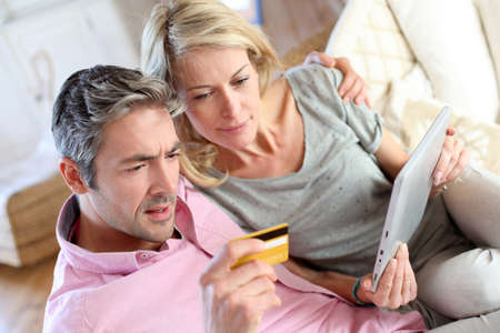 Couple sitting in sofa with electronic tablet photo