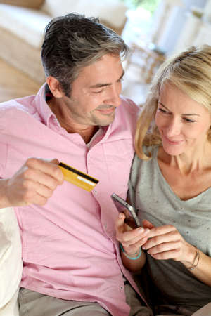 Upper view of couple paying with credit card on mobile phone photo