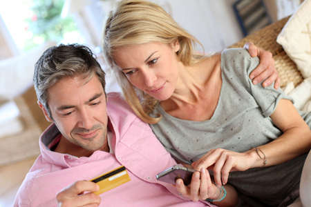 tarjeta de credito: Vista superior de una pareja de pagar con tarjeta de cr�dito en el tel�fono m�vil