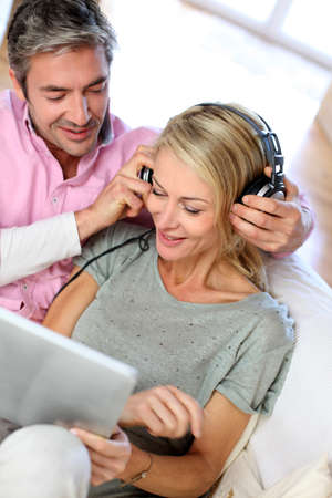 Couple listening to music at home with tablet photo