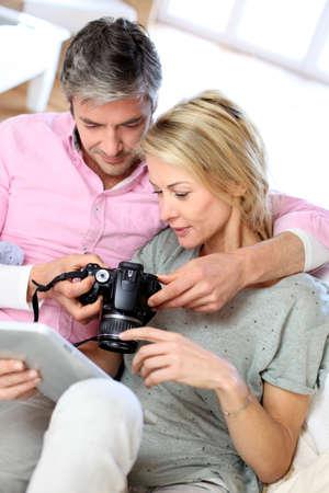 aficionado: Pareja en casa viendo fotos en la tableta electr�nica Foto de archivo
