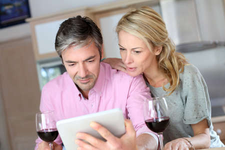 websurfing: Couple in kitchen with glass of wine websurfing on tablet Stock Photo