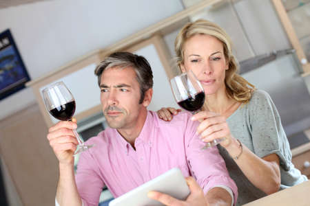 Couple in kitchen with glass of wine websurfing on tablet photo