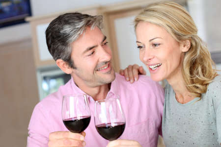 Happy couple in kitchen drinking red wine photo