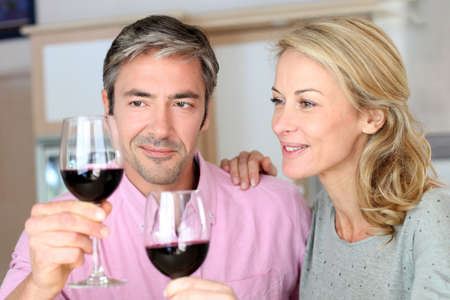 Couple drinking red wine in kitchen photo