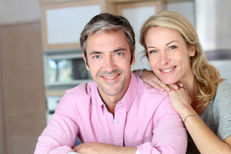 Cheerful couple leaning on kitchen counter photo