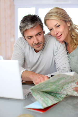 trip: Mature couple planning vacation trip with map and laptop