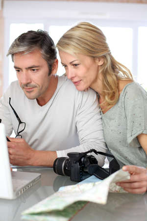 Mature couple planning vacation trip with map and laptop photo