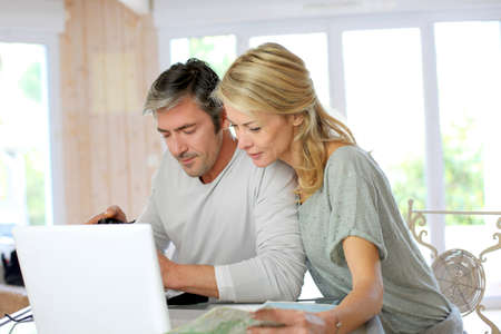 vacation map: Mature couple planning vacation trip with map and laptop
