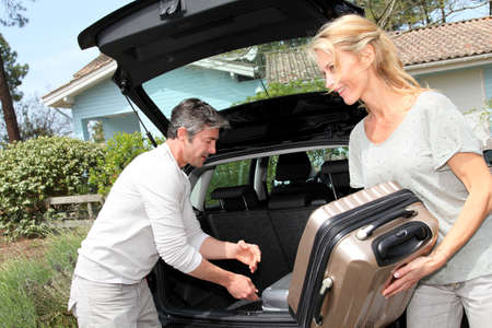 Couple putting suitcases in car trunk for a journey Stock Photo - 13949140