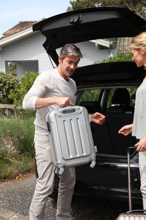 Couple putting suitcases in car trunk for a journey  photo