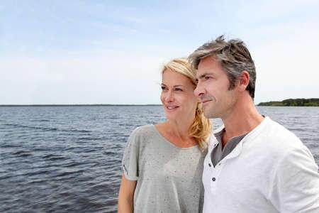mujer mirando el horizonte: Pareja abrazándose en un puente junto a un lago Foto de archivo