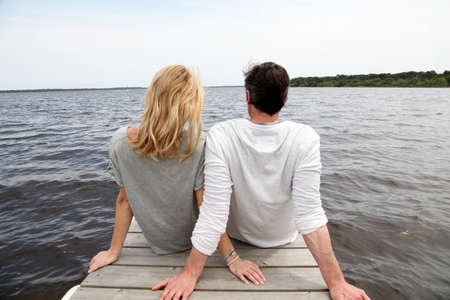 Rear view of couple sitting on a wooden bridge by a lake photo