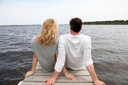 mujer mirando el horizonte: Vista trasera de la pareja sentada en un puente de madera por un lago