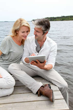 Couple sitting on boardwalk and using tablet photo