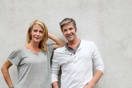40s adult: Modern couple standing on concrete wall Stock Photo