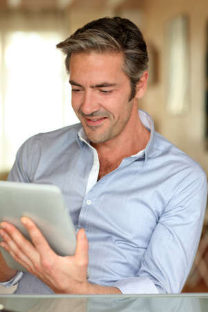 Handsome guy working from home with electronic tablet photo