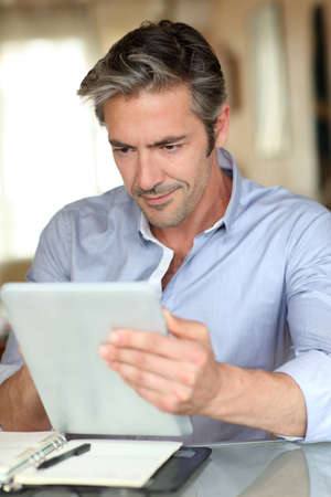 noting: Handsome guy working from home with electronic tablet
