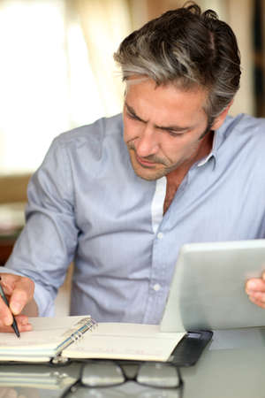 40s adult: Handsome guy working from home with electronic tablet