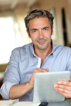 40s: Handsome guy working from home with electronic tablet