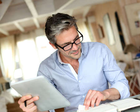 middle aged man: Handsome businessman with eyeglasses working from home Stock Photo