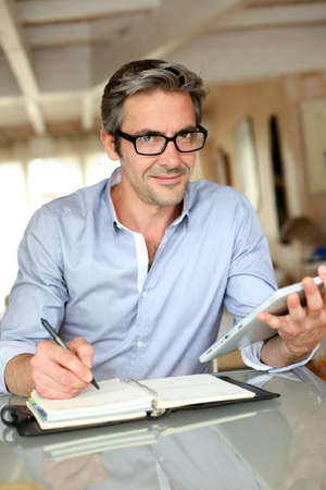 telework: Handsome businessman with eyeglasses working from home Stock Photo